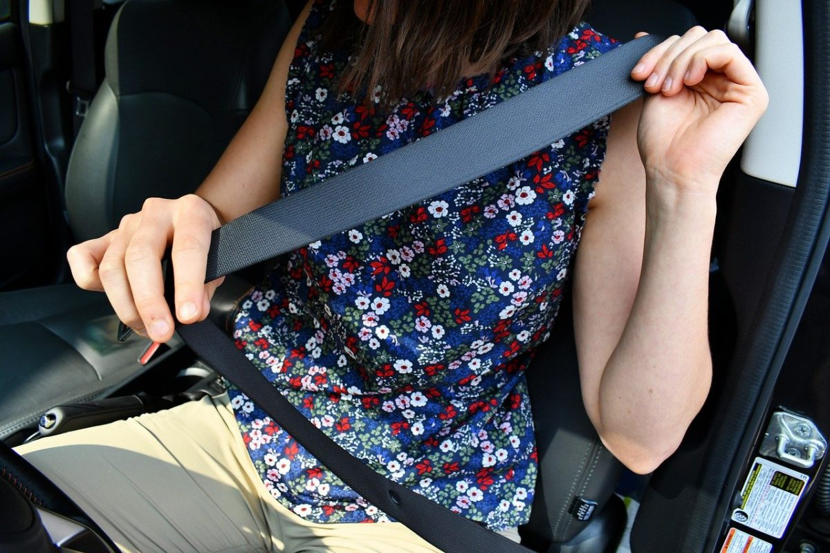 woman putting on her seat belt